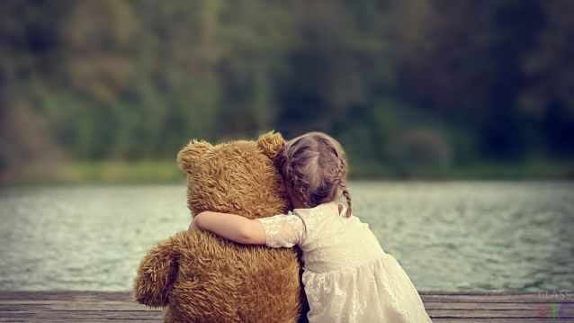 Девочка обняла плюшевого медведя